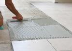 vakman is de vloer aan het tegelen